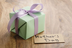 Green paper gift box with purple ribbon bow and mothers day greeting card on old wood table Stock Images