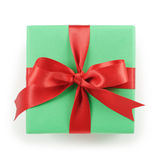 Green paper gift box with red ribbon bow top view on white background Stock Images