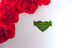 Green paper heart with wings and congratulation and red petals on white background. Green paper heart with wings and congratulation and red petals on white Stock Photo