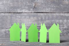 Green paper houses. On grey wooden table stock photography