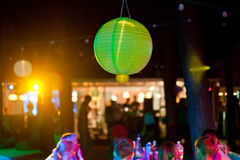 Green paper lantern outdoor party with people on background.  royalty free stock images