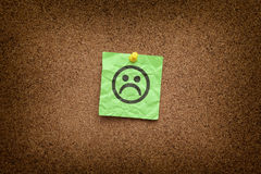 Green paper note with sad face on a cork board Stock Photos