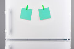 Green paper notes attached with stickers on white refrigerator Stock Photo