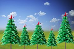 Green paper origami Christmas trees craft against natural landscape with blue sky stock photos