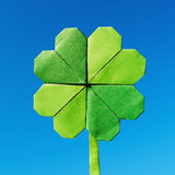 Green paper origami folded shamrock on blue sky background Royalty Free Stock Photo