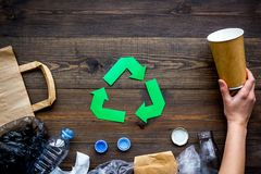 Green paper recycling sign among waste materials paper, plastic, polyethylene on dark wooden background top view copy. Green paper recycling sign among waste Royalty Free Stock Image