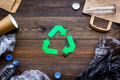 Green paper recycling sign among waste materials paper, plastic, polyethylene on dark wooden background top view copy. Green paper recycling sign among waste Stock Image