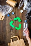 Green paper recycling sign among waste materials paper, plastic, polyethylene on dark wooden background top view copy. Green paper recycling sign among waste Stock Images