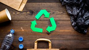 Green paper recycling sign among waste materials paper, plastic, polyethylene on dark wooden background top view copy. Green paper recycling sign among waste Stock Photos