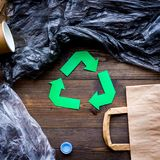 Green paper recycling sign among waste materials paper, plastic, polyethylene on dark wooden background top view close. Green paper recycling sign among waste Royalty Free Stock Photo