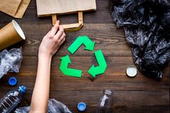 Green paper recycling sign among waste materials paper, plastic, polyethylene on dark wooden background top view.  Royalty Free Stock Images