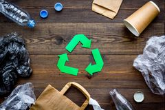 Green paper recycling sign among waste materials paper, plastic, polyethylene on dark wooden background top view.  Stock Photos