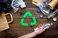Green paper recycling sign among waste materials paper, plastic, polyethylene on dark wooden background top view.  Stock Image