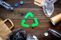 Green paper recycling sign among waste materials paper, plastic, polyethylene on dark wooden background top view.  Royalty Free Stock Image