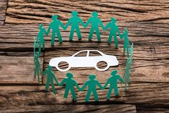 Free Green Paper Team Surrounding Car On Wooden Table Royalty Free Stock Image - 124524246
