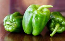 Green paprika / pepper on wooden broun table. Close up. Blur dark background royalty free stock photography