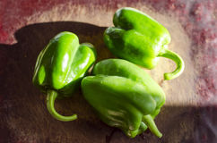 Green paprika / pepper on wooden broun table. Close up. Blur dark background royalty free stock images