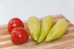 Green paprika and tomato on the cutting board Stock Photo