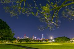 Green park and glowing night city stock photography