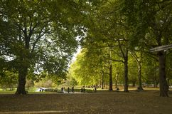 Green Park London Great Britain, October 16 2017. People walking in the park, Beautiful autumn day. Colorful trees and leafs lying on grass stock photo
