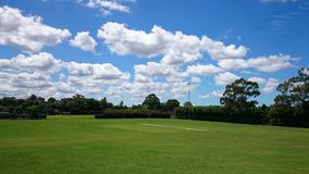 Green park outdoor with blue sky clouds. Beautiful grass ground, blue sky and white clouds at West Epping Park , Sydney Australia Stock Image