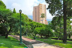 Green park and residential building in Monte Carlo, Monaco. Green lawns and trees of small urban park and modern residential building on background in Monte Stock Image