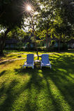 Green park and two chair with long shadows. From setting sun royalty free stock image