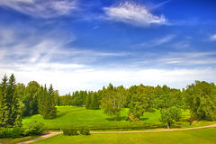 Green park under blue sky with clouds Royalty Free Stock Images