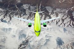 Green passenger plane in flight. Aircraft flies over snow-capped mountain peaks Royalty Free Stock Photos