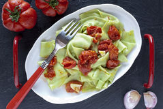 Green pasta with tomatoes Stock Image