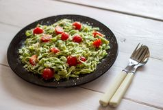 Green pasta with tomatoes and parmesan cheese. stock photo