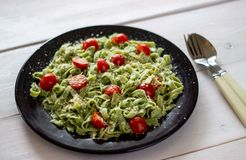 Green pasta with tomatoes and parmesan cheese. Top view. Green pasta with tomatoes and parmesan cheese. White background. Top view royalty free stock image