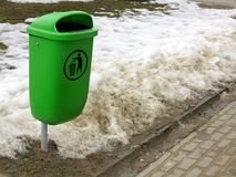 Green pastic garbage bin or can on street Stock Image