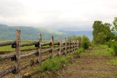 Green pasture and fence at mountains. Green pasture and wood fence in summer morning at mountains Tien Shan, fog after rain Stock Photography