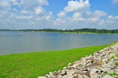 Green pasture and stones by a reservoir Royalty Free Stock Image