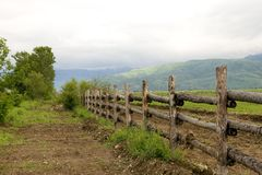 Green pasture and wood fence in summer morning Royalty Free Stock Image