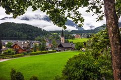 Green pastures of Alpine village Altaussee in a rainy morning. Green pastures of Alpine village Altaussee by the lake Altausseersee in a rainy morning with Stock Photo