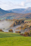 Green pastures and mountains on a spring foggy morning Stock Photo