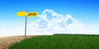 Green Pastures Sign. A meadow symmetrically cut with one side flourishing and green and the other withering and dying symbolising the saying greener pastures on Stock Photo