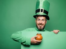 Green patricks background. Man in Patrick`s suit smiling. Man in Saint Patrick`s Day leprechaun party hat having fun on. Green background royalty free stock images