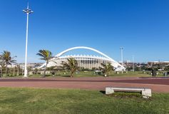 Green Pawn and paved Walkway against Moses Mabhida Stadium. DURBAN, SOUTH AFRICA - FEBRUARY 23, 2018: Morning view of empty green lawn and paved walkway against Royalty Free Stock Photo