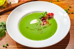 Green pea cream soup with bacon in white plate. royalty free stock image