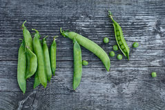 Green pea pods beautifully lie on vintage wooden surfaces. Top view stock image