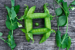 Green pea pods beautifully lie on vintage wooden surfaces royalty free stock image