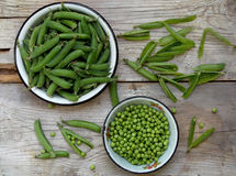 Green pea pods and cleaned in a metal bowl. On a wooden background stock images