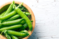 Green pea pods in wooden bowl Stock Images