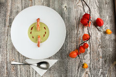 Green Pea and Prawn Soup. A delicious Green Pea Soup with Prawns, beautifully decorated with a branch of red flowers Royalty Free Stock Photography