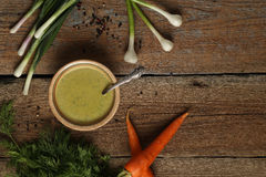 Green pea soup in a ceramic bowl, carrots, onion, garlic and herbs Stock Photo