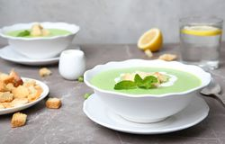 Green pea soup with croutons. In bowl on table stock photos
