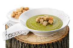 Green pea soup with croutons on the wooden stump Royalty Free Stock Images